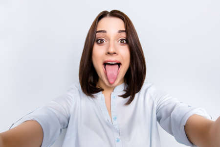 Photo for Self portrait of pretty, charming, comic, childish, funny girl with modern hairstyle gesture tongue out to the front camera shooting selfie with two hands, isolated on grey background - Royalty Free Image