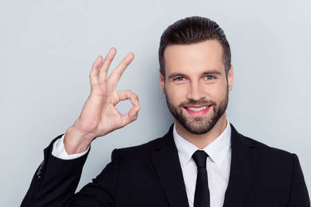 Photo for Close up portrait of cheerful excited handsome attractive friendly kind delightful with modern stylish fashionable hairstyle demonstrating ok symbol isolated on gray background - Royalty Free Image
