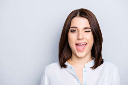 Foto de Close up portrait of nice, modern, trendy woman having short hair and open mouth, blinking with eye, isolated on grey background - Imagen libre de derechos