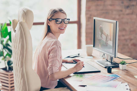 Photo pour Charming, pretty woman holding tablet pen, having colorful palette, using digitizer, sitting on armchair at desk in work station, making, drawing sketch, looking at camera - image libre de droit