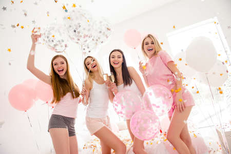 Foto de Cheerful slim pretty stylish charming funky girls in night wear in rain of colorful stars, confetti enjoying meeting indoor drinking alcohol laughing standing and looking at camera sleepover party - Imagen libre de derechos