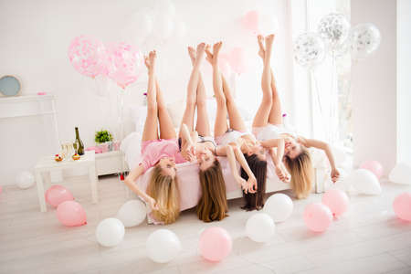 Foto de Charming, pretty, cheerful, foolish, attractive, sexy, slender girls lying head over heels on bed with raised crossed legs, holding hands, celebrating birthday, holiday, event, looking at each other - Imagen libre de derechos
