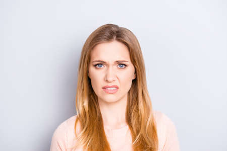 Foto de Close up portrait of funny confused puzzled unhappy upset sad uncertain unsure beautiful pretty charming grimacing woman with long blonde hairdo isolated on gray background copy-space - Imagen libre de derechos