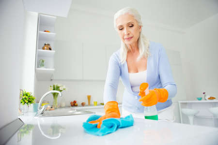 Foto de Portrait of beautiful charming neat, cleanly attractive woman in orange protective gloves rubbing tabletop, countertop with rag using spray in apartment flat - Imagen libre de derechos