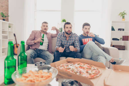 Photo pour Portrait of attractive, stylish guys with modern hairstyle watching soccer word cup with excited expression drinking alcohol beverage, eating pizza, chips, snack, sitting in livingroom - image libre de droit