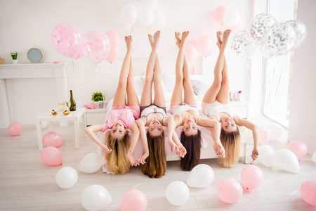 Photo for Charming, pretty, cheerful, foolish, attractive, sexy, slender girls lying head over heels on bed with raised crossed legs, holding hands, having dress-code looking at camera - Royalty Free Image