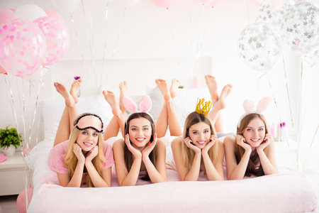 Photo for Cheerful, charming, pretty, cute, blonde, brunette models laying on stomach with raised crossed feet looking at camera holding hands near face, enjoying gathering, meeting indoor on sleepover party - Royalty Free Image