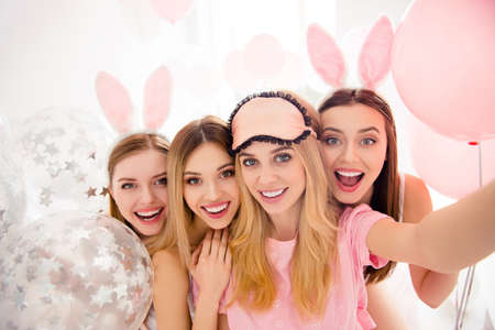 Photo for Self portrait of pretty, attractive, charming, cheerful, funny, cute girls shooting selfie on front camera enjoying meeting indoor, celebrating event with air balloons, having rabbit ears and eye mask - Royalty Free Image