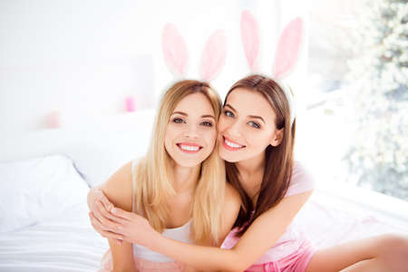 Foto de Portrait of pretty, successful, confident, cute girls with beaming smiles, wearing rabbit ears, hugging with arms, looking at camera, spending time together indoor, in house - Imagen libre de derechos
