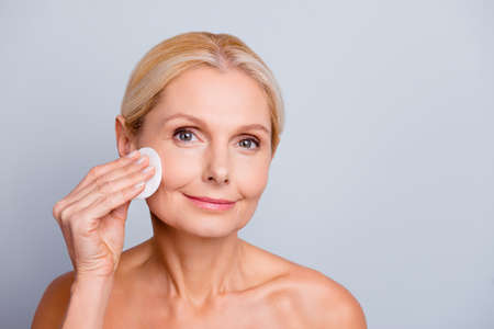 Foto de Portrait of pretty charming stylish attractive woman with wrinkle applying lotion using cotton pad cleaning make-up looking at camera isolated on grey background - Imagen libre de derechos