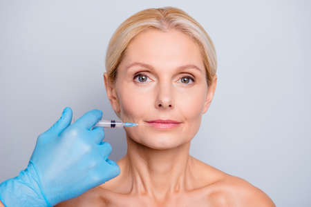 Photo pour Portrait of calm serious aged woman with wrinkle making augmentation injection in lips in clinic salon isolated on grey background enhancement concept - image libre de droit