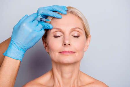 Photo pour Portrait of calm serious aged woman with wrinkle keeping eyes close getting injection in forehead in professional clinic isolated on grey background - image libre de droit