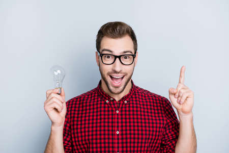 Foto de Yes! Genial ideas are the most obvious! Close up of thoughtful minded cheerful delighted handsome astonished amazed wondered guy holding light bulb, completed task, isolated on gray background - Imagen libre de derechos