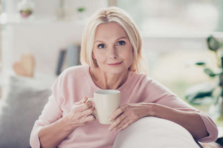 Photo for Modern, stylish, caucasian, aged, woman having cup of coffee in the morning, sitting on sofa in living room at home, looking at camera - Royalty Free Image
