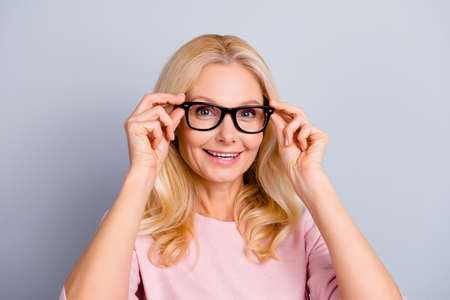 Photo for Portrait of cheerful positive charming attractive cute woman with wrinkle holding eyelets with two hands of glasses on her face looking at camera isolated on grey background - Royalty Free Image