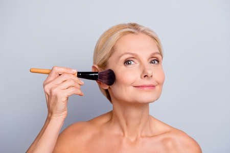 Photo pour Portrait of charming woman with smooth soft perfect skin applying rouge with brush on cheek looking at camera isolated on grey background - image libre de droit
