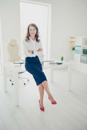 Photo for Portrait of pretty, charming, sexy, trendy, brunette, positive director, boss with curls, hairdo wearing stilettos shoes having her arms crossed looking at camera, modern interior - Royalty Free Image