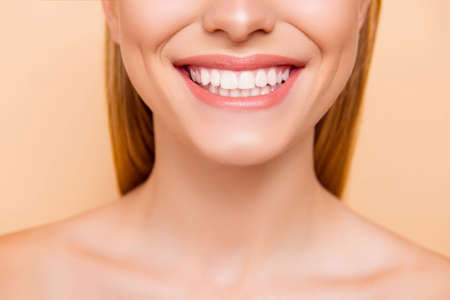 Foto de Close up cropped half face portrait of attractive, nude, natural, perfect, ideal girl with healthy white teeth isolated on beige background, perfection, wellness, wellbeing, restoration concept - Imagen libre de derechos