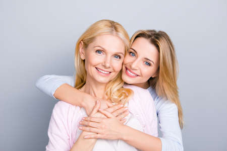 Foto de Portrait of stylish cute attractive charming mother and daughter, family with one single parent, warm hugs, looking at camera isolated on grey background - Imagen libre de derechos