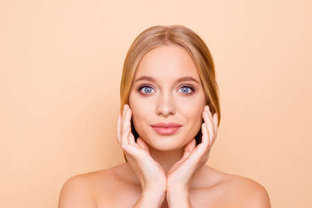 Photo pour Big eyed, charming, pretty, cute, lovely girl enjoying her perfect face skin after mask, lotion, peeling, cream, balm, holding hands on cheek, isolated on beige background, wellness wellbeing concept - image libre de droit