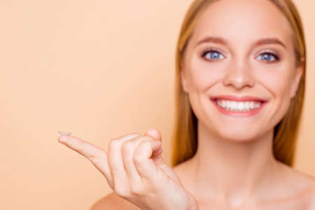 Photo pour Portrait of pretty, charming, cheerful, positive, joyful, toothy girl on blurred background holding focused crystalline lens on index finger isolated on beige background - image libre de droit