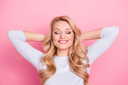 Foto de Portrait of positive cheerful girl with modern hairdo natural makeup beaming smile holding hands behind the head keeping eyes closed dreaming about journey, trip, traveling - Imagen libre de derechos