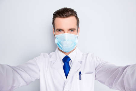 Foto de Self portrait of creative funny dentist in white lab coat, blue, tie, protective face mask shooting selfie on smart phone, having rest relax video call, isolated on grey background - Imagen libre de derechos