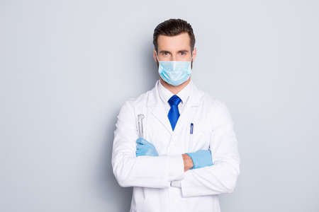 Foto de Portrait of attractive handsome dentist with hairstyle in protective face mask, white lab coat, blue tie, holding equipments in crossed arms, isolated on grey background - Imagen libre de derechos