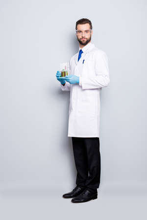 Foto de Full size fullbody portrait of attractive stylish scientist in white lab coat, black pants, shoes, tie holding test tubes with multi-colored liquid, looking at camera, isolated on grey background - Imagen libre de derechos