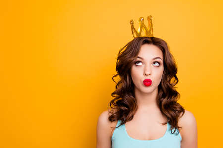 Foto de Portrait with copyspace empty place of funny stupid girl looking at crown on head with eyes sending kiss with pout lips isolated on yellow background advertisement concept - Imagen libre de derechos