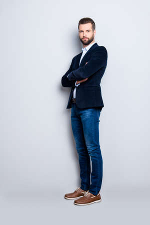 Photo pour Full size body portrait of elegant trendy teacher with stubble having his arms crossed looking at camera isolated on grey background, wearing jacket, jeans, shirt - image libre de droit