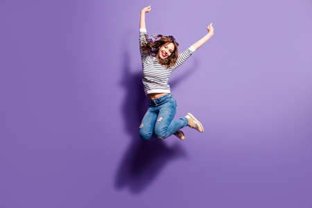 Foto de Portrait of cheerful positive girl jumping in the air with raised fists looking at camera isolated on violet background. Life people energy concept - Imagen libre de derechos