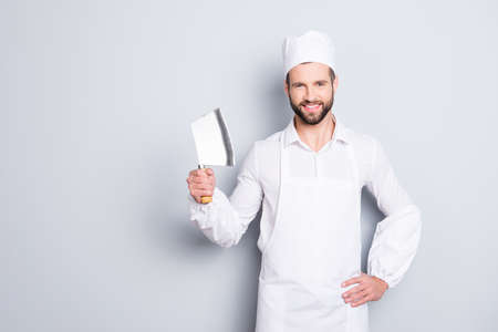 Foto de Portrait of positive cheerful handsome butcher having cleaver in arm holding hand on waist, looking at camera, isolated on grey background - Imagen libre de derechos