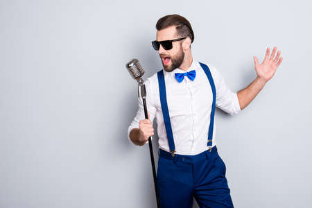 Photo for Portrait of handsome attractive singer in blue pants with suspenders and black glasses, singing hit with open mouth in microphone gesture with hand isolated on grey background - Royalty Free Image