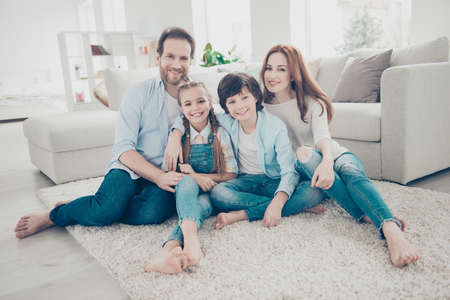 Photo pour Portrait of lovely cheerful family with two kids in casual outfits sitting on carpet near sofa in modern white livingroom looking at camera. Domicile domestic lifestyle rest relax leisure concept - image libre de droit