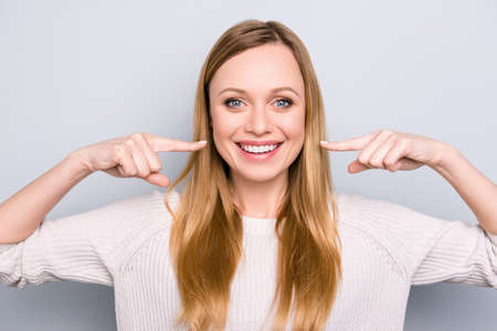 Foto de Portrait of joyful satisfied girl gesturing her beaming white healthy teeth with two forefingers looking at camera isolated on grey background. Orthodontic concept - Imagen libre de derechos