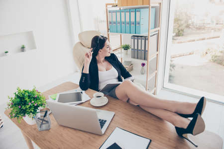 Photo pour Portrait of dreamy pensive woman putting sexy legs on table wearing stilettos looking at window having notepad and pen in hands dreaming about vacation weekend planning journey trip - image libre de droit