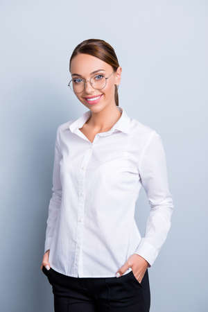Photo pour Vertical portrait of pretty cute girl in eyeglasses wearing classic white shirt holding two hands in pockets of black pants looking at camera isolated on grey background - image libre de droit
