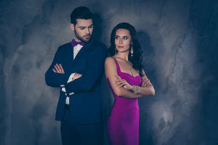 Photo for He vs she! Portrait of couple standing back to back holding arms crossed looking at each other isolated on grey background, pretty hispanic latin lady in tight purple dress gentleman in tux with bow - Royalty Free Image