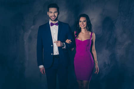 Photo pour Portrait of positive cheerful lady with hairstyle curls and positive man with bristle in blue tuxedo famous lovely couple looking at camera isolated on dark grey background with shadow - image libre de droit