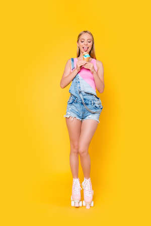 Photo for Fullbody vertical portrait of hungry slim girl in jeans overall on roller skates licking ice-cream with tongue out isolated on vivid yellow background - Royalty Free Image