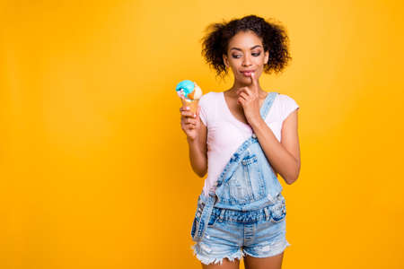 Foto de Portrait with copy space of foxy dreamy girl in jeans overall looking at ice cream in waffle cone holding finger on chin isolated on yellow background. Weight loss healthy lifestyle concept - Imagen libre de derechos
