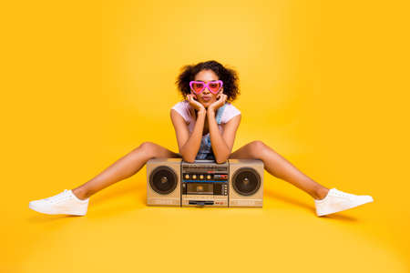 Foto de Portrait of sexy charming girlfriend in eyewear having boom box sending kiss with pout lips at camera isolated on yellow background. Leisure rest relax concept - Imagen libre de derechos