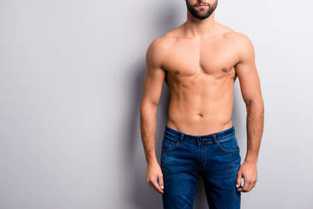 Foto de Cropped close up photo of handsome attractive ideal perfect stunning strong muscular flawless man's body with six-pack wearing dark blue denim jeans isolated on gray background copy-space - Imagen libre de derechos