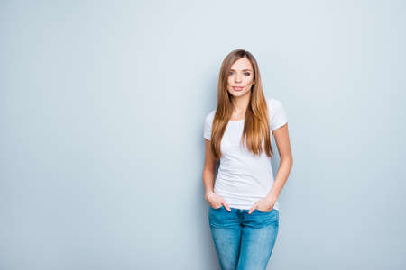 Photo for Portrait with copyspace empty place of sexy nice girl in white t-shirt holding two hand in pocket of pants isolated on grey background looking at camera - Royalty Free Image