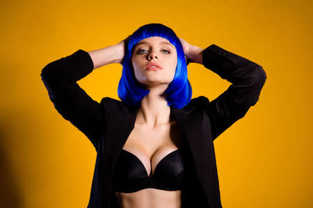 Photo for Portrait of hot confident woman with big boobs in black jacket bright blue wig holding hands behind head isolated on yellow background - Royalty Free Image