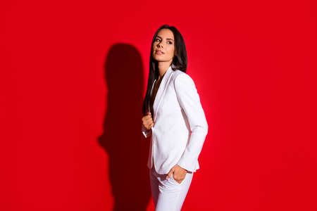 Foto de Side view portrait of gorgeous charming woman in white suit holding hand in pocket looking away isolated on bright red background - Imagen libre de derechos