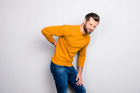 Foto de Side profile half-turned portrait of grimacing sad upset unhappy with serious pain in back man wearing yellow tight sweater and jeans isolated on gray background copy-space - Imagen libre de derechos