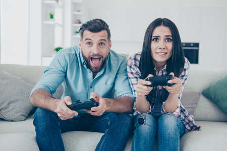 Foto de Portrait of funny comic couple holding joy sticks in hands playing video game enjoying activity sitting on sofa indoors - Imagen libre de derechos