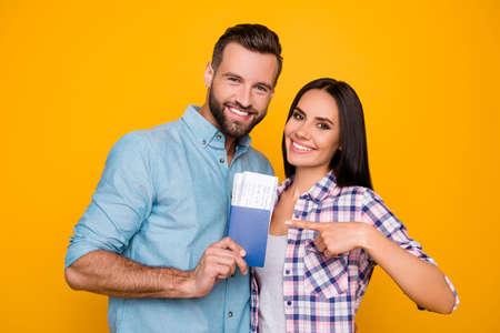 Photo for Portrait of joyful glad couple holding passport with flying tickets in hands pointing with forefinger looking at camera isolated on bright yellow background - Royalty Free Image